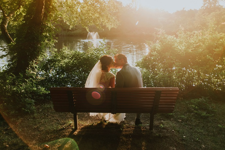 man and women kissing on bench